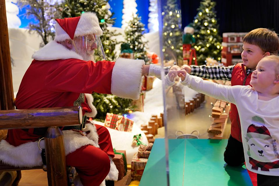 Julianna, 3, and Dylan, 5, Lasczak visit with Santa through a transparent barrier at a Bass Pro Shop in Bridgeport, Conn., Tuesday, Nov. 10, 2020. Santa Claus is coming to the mall — just don't try to sit on his lap. Malls are doing all they can to keep the jolly old man safe from the coronavirus, including banning kids from sitting on his knee, no matter if they've been naughty or nice. (AP Photo/Seth Wenig) ORG XMIT: CTSW607