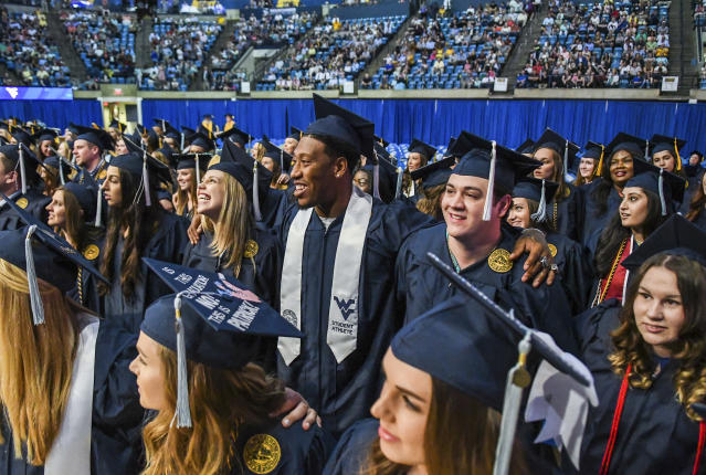 "In this May 12, 2018, photo released by West Virginia University, former West Virginia University and current Oakland Raiders football player Bruce Irvin, center, smiles as he stands arm-in-arm with fellow graduates during the singing of ""Country Roads"" at the conclusion of the College of Education and Human Services Commencement in the Coliseum in Morgantown, W.Va. When Irvin got a multimillion signing bonus after being a first-round draft pick in 2012, the idea of getting his college degree was the last thing on his mind. But after having a son, the former high school dropout made getting that degree a priority and was one of many NFL players this offseason who got to don a cap and gown instead of a helmet. (West Virginia University/Geoff Coyle via AP)"