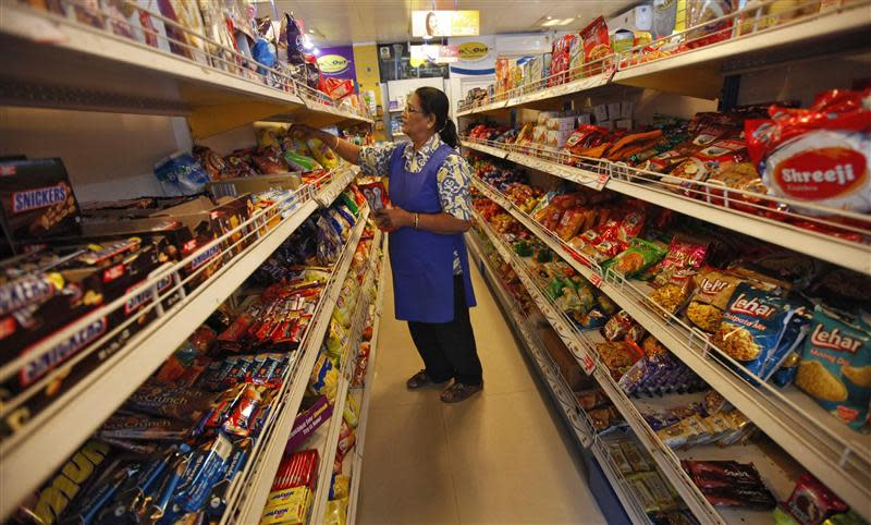A worker arranges food packets inside a retail store in Kolkata
