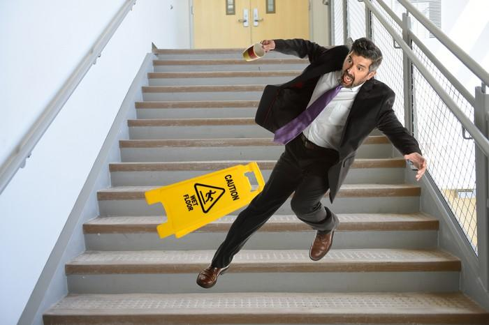 Man in suit trips on stairs next to a caution sign