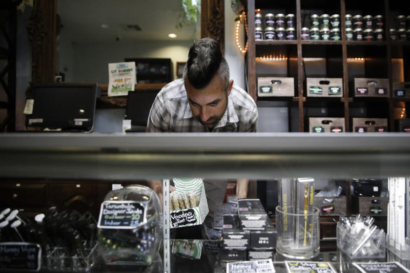FILE - In this June 27, 2017, file photo, Jerred Kiloh, owner of the licensed medical marijuana dispensary Higher Path, stocks shelves with with cannabis products in Los Angeles. More than three years after California voters approved broad legalized marijuana, a state panel is considering if the potent high-inducing chemical THC found in pot should be declared a risk to pregnant women and require warnings to consumers. (AP Photo/Jae C. Hong, File)