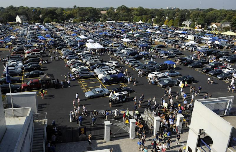 Football fans arrive and tailgate in the parking lot before the NCAA college football game between Navy and Air Force, Saturday, Oct. 5, 2013, in Annapolis, Md. (AP Photo/Nick Wass)