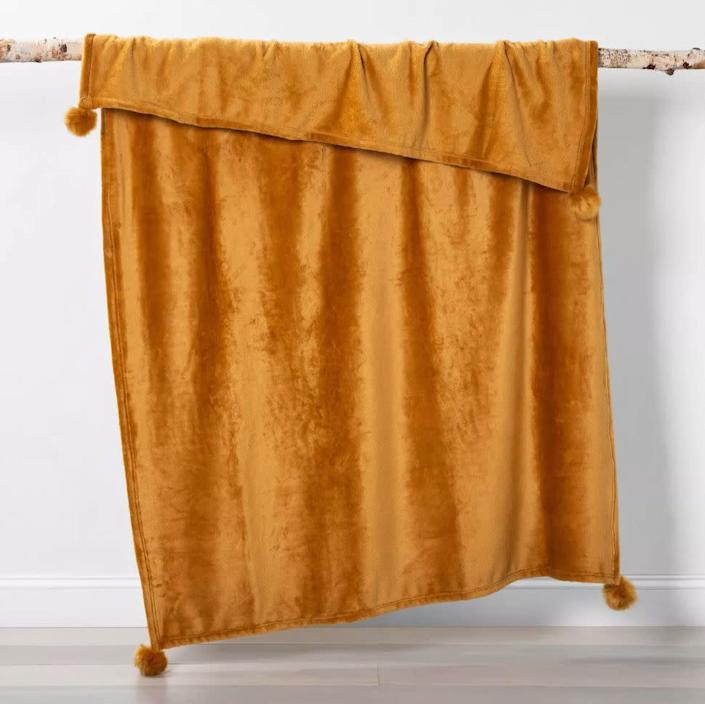 """You really don't lose sleep over the price tag of this blanket: $9. It comes in nine colors, from green to gold, and is edged with furry pom poms. <strong><a href=""""https://fave.co/359e54o"""" rel=""""nofollow noopener"""" target=""""_blank"""" data-ylk=""""slk:It's on sale right now at Target"""" class=""""link rapid-noclick-resp"""">It's on sale right now at Target</a></strong>.&nbsp;"""