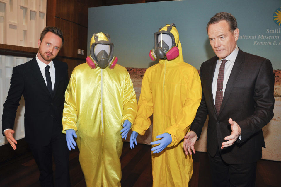 """WASHINGTON, DC- NOVEMBER 10: Actors Aaron Paul and Bryan Cranston pose with their Tyvek suits during a donation ceremony of artifacts from AMC's """"Breaking Bad"""" show at Smithsonian's National Museum of American History  in Washington DC on November 10, 2015.  (Photo by Kris Connor/Getty Images)"""