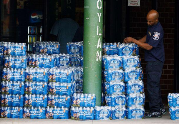 PHOTO: A city worker piles packages of bottled water being offered to area residents at a city-run bottled water distribution site at a community center in Newark, N.J., Aug. 16, 2019. (Justin Lane/EPA via Shutterstock)