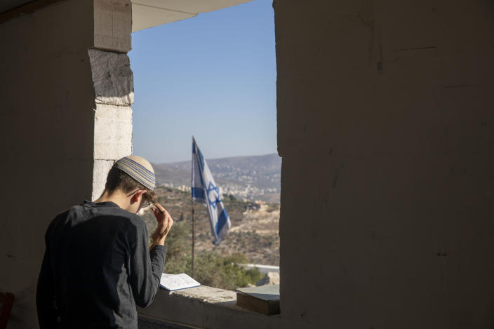 An Israeli settler prays in a synagogue at the outpost of Eviatar near the northern Palestinian West Bank town of Nablus, Sunday, June 27, 2021. Palestinians from the West Bank town of Beita have been holding regular protests against Eviatar, the nearby Jewish settlement outpost that was rapidly established last month. The Palestinians say it was established on their farmland. At least four protesters have been killed in clashes with Israeli troops. (AP Photo/Ariel Schalit)