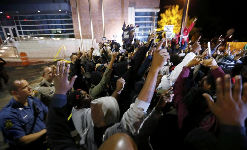 Protesters participate in a rally for Michael Brown outside the police department in Ferguson Missouri