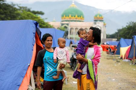 A family is seen outside their tent at a camp for displaced victims of the earthquake and tsunami in Palu, Central Sulawesi, Indonesia, October 9, 2018. REUTERS/Jorge Silva