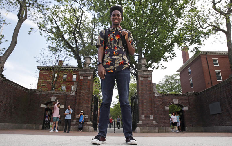 """Obasi Shaw poses outside the gates of Harvard Yard in Cambridge, Mass., Thursday, May 18, 2017. Shaw, an English major who graduates from Harvard next week, is the university's first student to submit his final thesis in the form of a rap album. The record, called """"Liminal Minds,"""" has earned the equivalent of an A- grade, good enough to ensure that Shaw will graduate with honors at the university's commencement next week. (AP Photo/Charles Krupa)"""