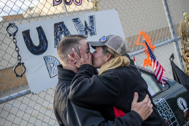 Clio resident Dawn Dekalita, 48, and a 16-year employee at the Flint Assembly Plant, plants a kiss on Shop Committee's Dustin Culhane in celebration as the United Auto Workers strike against General Motors comes to an emotional close outside of the Flint Assembly Plant, Friday, Oct. 25, 2019, in Flint, Mich. Striking General Motors factory workers are putting down their picket signs after approving a new contract that will end a 40-day strike that paralyzed the company's U.S. production. (Jake May/MLive.com/The Flint Journal via AP)