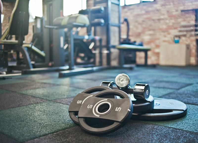Barbell, dumbbells lie on the floor against the background of the gym.