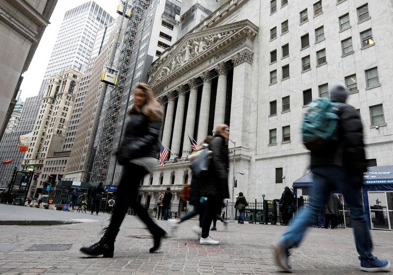 People walk on Wall Street in front of the New York Stock Exchange (NYSE) in New York, U.S., February 6, 2018. REUTERS/Brendan McDermid -