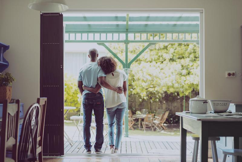 A photo of young couple standing arms around at entrance. Full length rear view of couple are in casuals. Satisfied loving man and woman spending quality time together at home.
