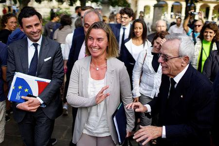 European Union's diplomat Federica Mogherini speaks to Eusebio Leal, a leading intellectual and the official historian of the city of Havana as they walk through Old Havana