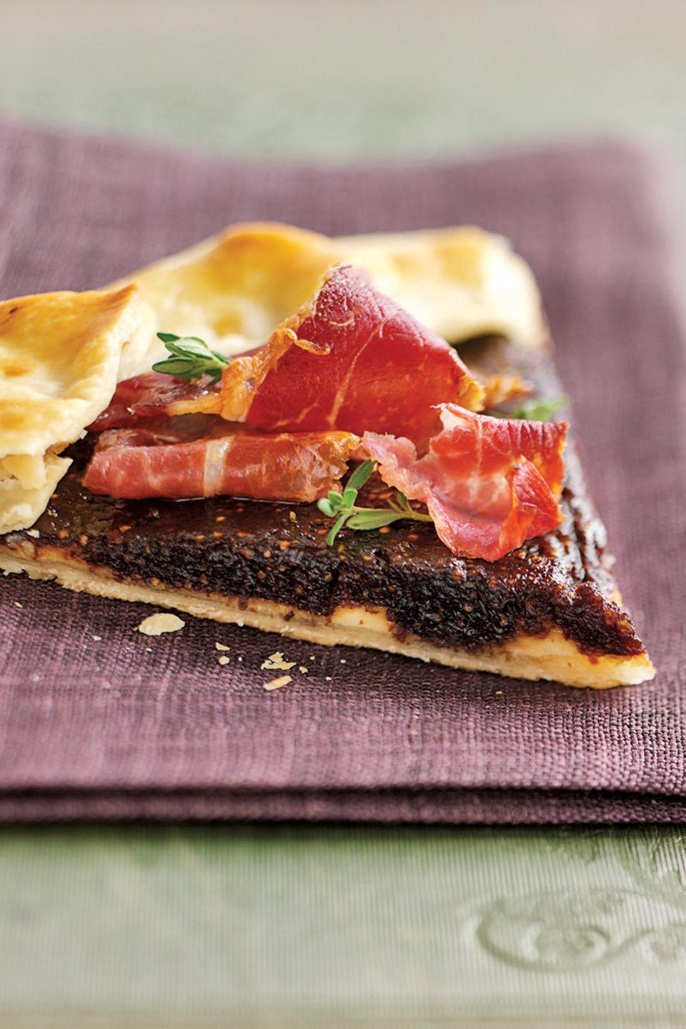 """<p>Expand your party menu with dependable staples from the pantry. Dried figs and prepared piecrust combine to make a sophisticated hors d'oeuvre. </p><p><strong><a href=""""https://www.countryliving.com/food-drinks/recipes/a1741/prosciutto-fig-crostata-3864/"""" rel=""""nofollow noopener"""" target=""""_blank"""" data-ylk=""""slk:Get the recipe"""" class=""""link rapid-noclick-resp"""">Get the recipe</a>.</strong></p>"""