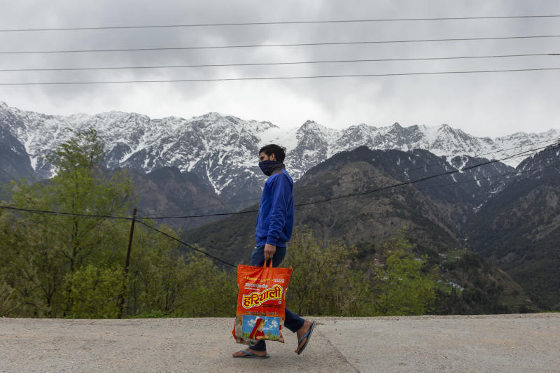Snow-covered peaks of the Dhauladhar range of the Himalaya are seen in the background as a man carries rations from a shop during a relaxation in the curfew put in place to check the spread of the coronavirus in Dharmsala, India, Tuesday, April 7, 2020. The new coronavirus causes mild or moderate symptoms for most people, but for some, especially older adults and people with existing health problems, it can cause more severe illness or death. (AP Photo/Ashwini Bhatia)