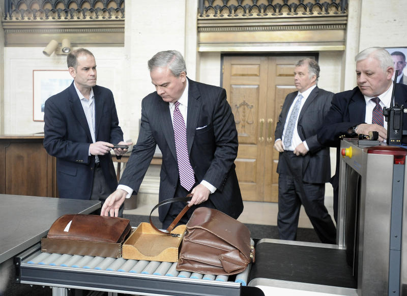 Former Connecticut Gov. John G. Rowland collects his belt and brief case after going through security at federal court, Friday, April 11, 2014, in New Haven, Conn. A grand jury on Thursday returned a seven-count indictment alleging Rowland schemed to conceal involvement with congressional campaigns. (AP Photo/Jessica Hill)