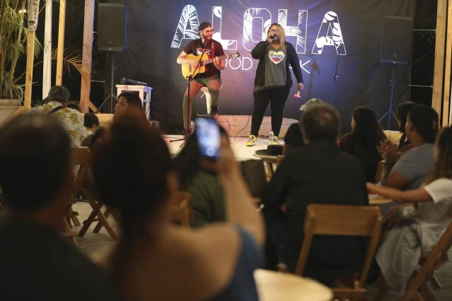 In this Jan. 12, 2019 photo, Venezuelan singer Reymar Perdomo performs with fellow Venezuelan and guitarist Omar Rumbos at a fair on the beach of San Bartolo, Peru. A year ago, Perdomo was singing for spare change on jammed buses, struggling to make ends meet while building a new life in Peru's capital. (AP Photo/Martin Mejia)