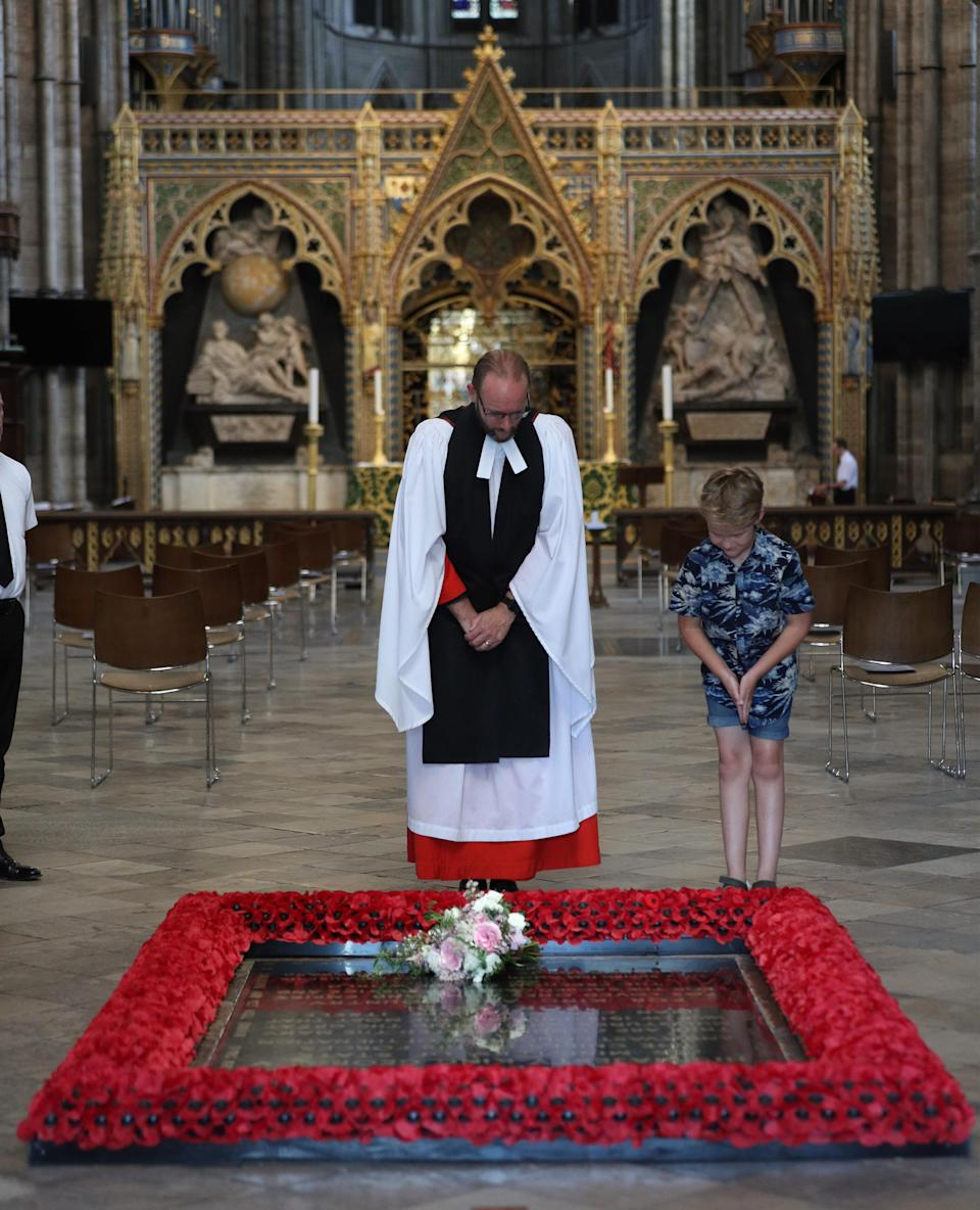 Reverend Anthony Ball, Canon of Westminster in Westminster Abbey in London with Toby Wright, son of the Reverend Paul Wright, Sub-Dean of the Chapel Royal, laying the bouquet. (PA Images)