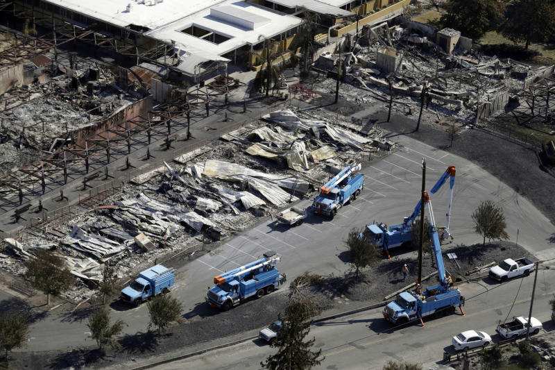 """FILE - In this Oct. 14, 2017, file photo, Pacific Gas & Electric crews work on restoring power lines in a fire ravaged neighborhood in an aerial view in the aftermath of a wildfire in Santa Rosa, Calif. A Wednesday, July 10, 2019, report in the Wall Street Journal says Pacific Gas & Electric, which is blamed for some of California's deadliest recent fires, knew for years that dozens of its aging power lines posed a wildfire threat but avoided replacing or repairing them. PG&E says it disagrees with the Journal's conclusions but says it's """"taking significant actions to inspect, identify, and fix"""" safety issues. (AP Photo/Marcio Jose Sanchez, File)"""