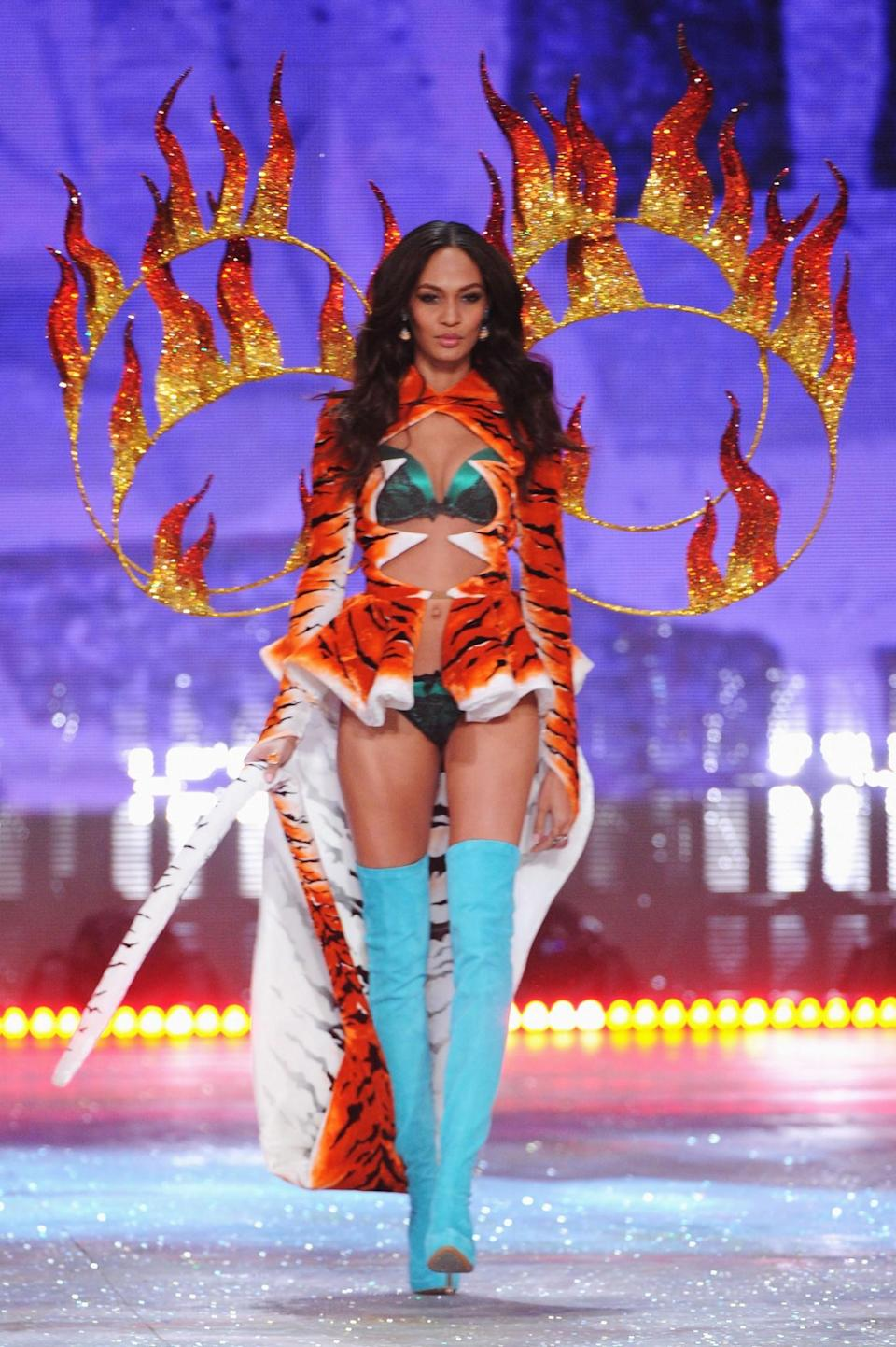 <p>Joan Smalls modelled a very wild outfit in 2012, complete with a tiger print cape and fire rings. [Photo: Getty] </p>
