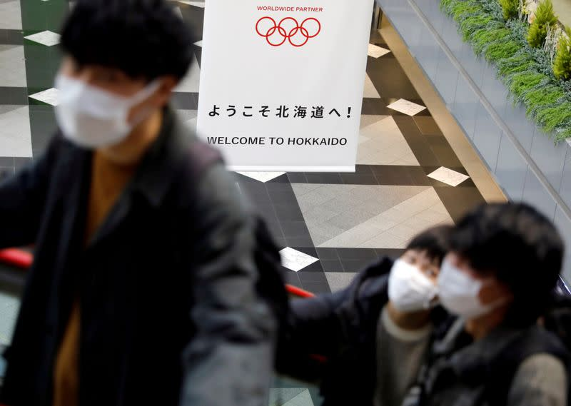 FILE PHOTO: Passengers wearing protective face masks, following an outbreak of the coronavirus, are seen near a campaign banner for Tokyo 2020 Olympic Games  at New Chitose Airport in Chitose, Hokkaido