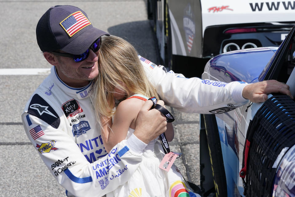 Dale Earnhardt Jr., comforts his daughter Isla, 3, during driver introductions prior to the start of the NASCAR Xfinity auto race in Richmond, Va., Saturday, Sept. 11, 2021. (AP Photo/Steve Helber)