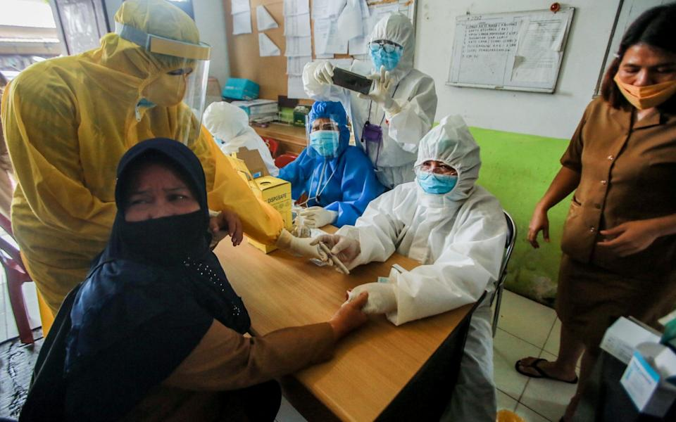 Healthcare workers clad with hazmat suits collect blood samples from a women during an antibody rapid test for coronavirus in Medan, North Sumatra, Indonesia - Dedi Sinuhaji/EPA-EFE/Shutterstock
