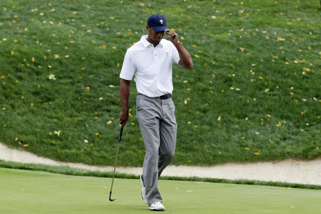 United States team player Tiger Woods acknowledges the gallery after putting on the 17th hole during the single matches at the Presidents Cup golf tournament at Muirfield Village Golf Club Sunday, Oct. 6, 2013, in Dublin, Ohio. (AP Photo/Darron Cummings)