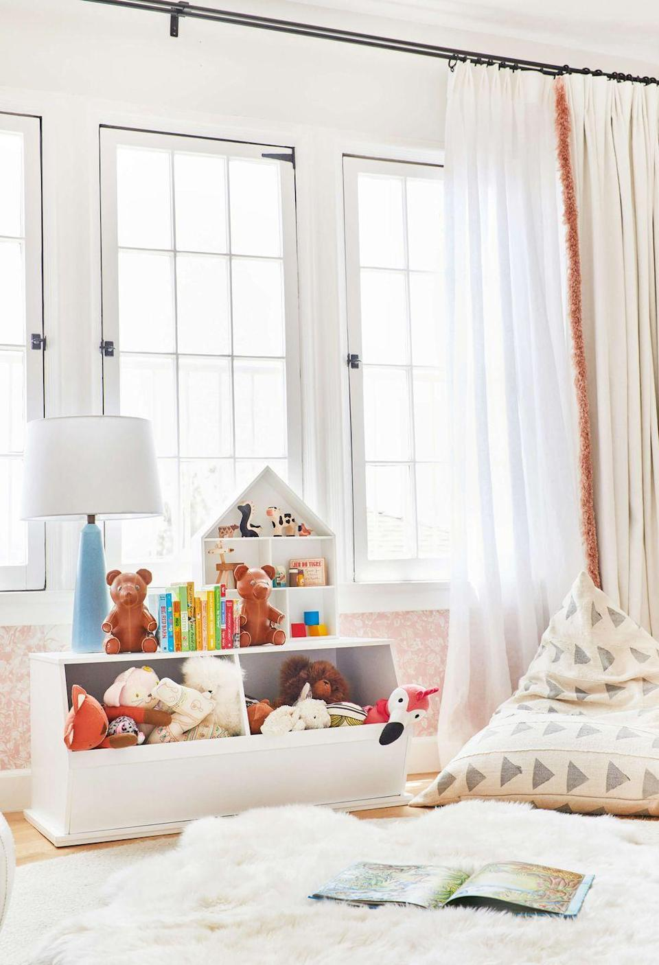 """<p>Keep shelving units for smaller kids' rooms low to the ground to prevent heavier toys from falling down.</p><p><strong>See more at <a href=""""https://stylebyemilyhenderson.com/blog/elliots-nursery-reveal"""" rel=""""nofollow noopener"""" target=""""_blank"""" data-ylk=""""slk:Emily Henderson"""" class=""""link rapid-noclick-resp"""">Emily Henderson</a>.</strong></p><p><strong><strong><strong><a class=""""link rapid-noclick-resp"""" href=""""https://www.amazon.com/s?k=plastic+storage+bins&ref=nb_sb_noss_2&tag=syn-yahoo-20&ascsubtag=%5Bartid%7C10063.g.36014277%5Bsrc%7Cyahoo-us"""" rel=""""nofollow noopener"""" target=""""_blank"""" data-ylk=""""slk:SHOP PLASTIC STORAGE BINS"""">SHOP PLASTIC STORAGE BINS</a></strong></strong><br></strong></p>"""