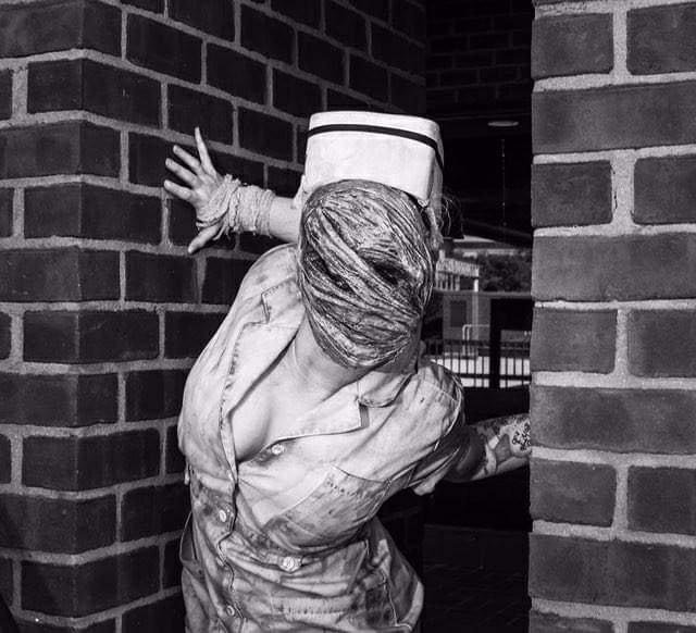 woman doing cosplay as silent hill nurse. her arms are hyperextending due to ehlers-danlos syndrome