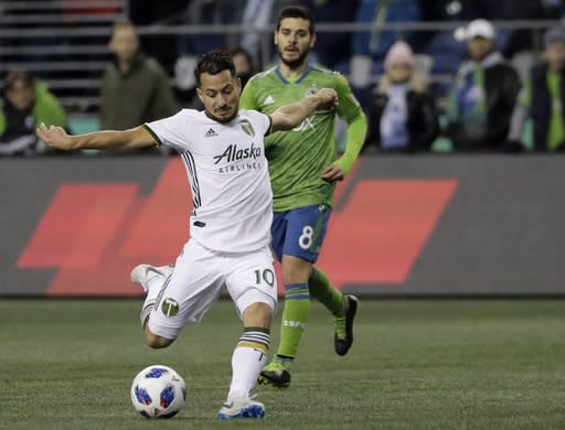 Portland Timbers midfielder Sebastian Blanco (10) takes a shot as Seattle Sounders midfielder Victor Rodriguez, rear, watches during the first half of the second leg of an MLS soccer playoff series Thursday, Nov. 8, 2018, in Seattle. (AP Photo/Ted S. Warren)