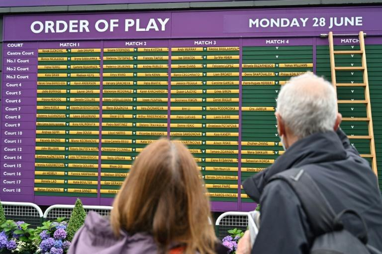 Welcome back: Spectators look at the order of play board on the first day of Wimbledon on Monday