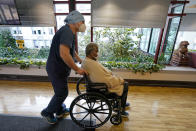 Patricia Marson is wheeled back to her room by nurse manager Rob Treiber after she became the first patient at Hebrew Rehabilitation Center to receive a COVID-19 vaccine, Wednesday, Dec. 30, 2020, in Boston. (AP Photo/Elise Amendola)