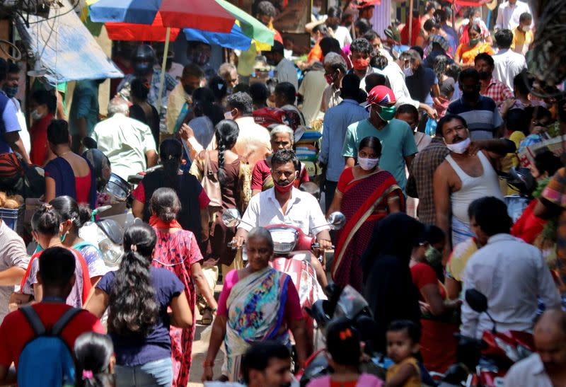 People are seen at a crowded marketplace in a slum area in Mumbai