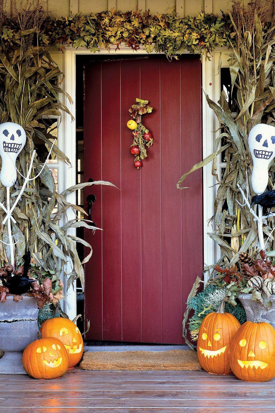 """<p>Give trick-or-treaters and guests a festive first impression, framing the front door with these skeletal gourds. These bottle-gourd scarecrows were painted white, with features added in black felt tip pen. Just spear them on sticks and """"plant"""" them in Styrofoam blocks inside urns to create a festive welcome to your Halloween home. </p>"""