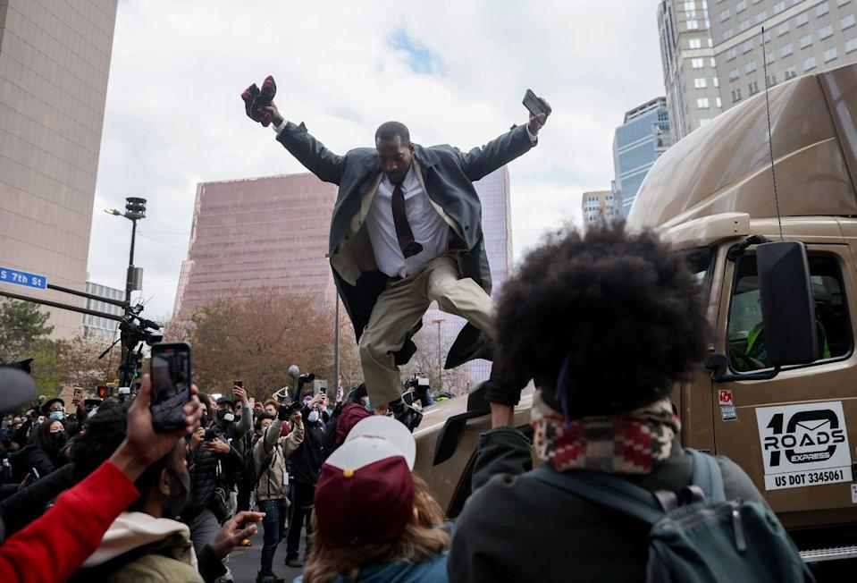 <p>A man jumps down from a truck which had attempted to make its way past the crowd as people react after the verdict was read.</p>