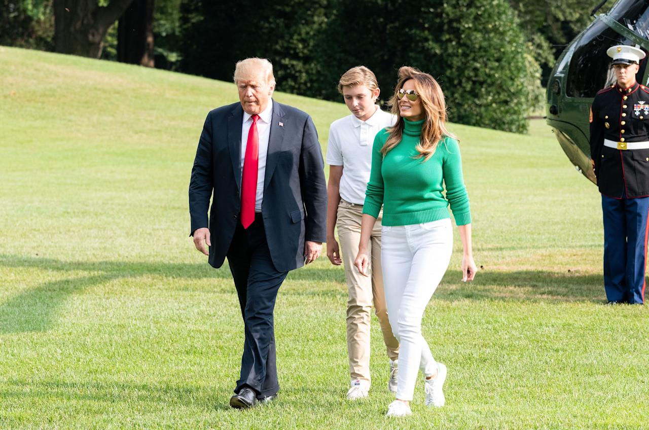 <p>Crossing the White House lawn with her husband, the President, and son, Baron, Melanie kept it casual in white skinny jeans and a bright green poloneck jumper. <br /><em>[Photo: Rex]</em> </p>