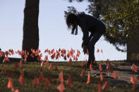 CORRECTS SPELLING OF LAST NAME ON FIRST REFERENCE - Cindy Pollock does maintenance on the construction flags in her front yard in Boise, Idaho, on Wednesday, Feb. 10, 2021. Pollock began planting the tiny flags across her yard — one for each of the more than 1,800 Idahoans killed by COVID-19 — the toll was mostly a number. Until two women she had never met rang her doorbell in tears, seeking a place to mourn the husband and father they had just lost. (AP Photo/Otto Kitsinger)