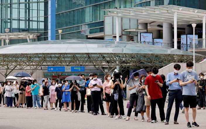 People wait in line for a coronavirus disease (COVID-19) test at a testing site, temporarily set up at a railway station in Seoul, South Korea, July 7, 2021. - Reuters