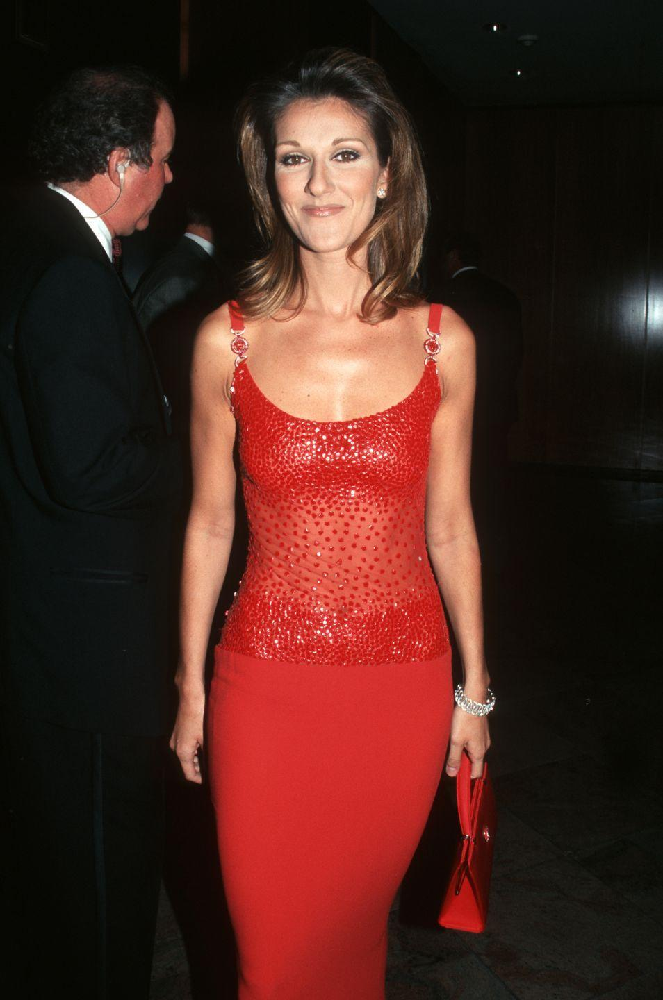 <p>Feeling red hot in the middle of summer, Celine wore a form-fitting red gown with a netted bodice to the Tony Awards in New York City. Please note the envy-inducing matching red purse, too.</p>