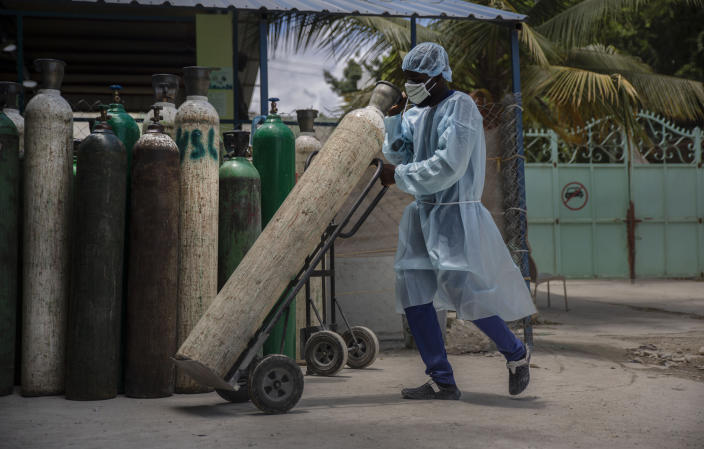 FILE - In this June 5, 2021, file photo, a hospital employee wearing protective gear transports oxygen tanks in Port-au-Prince, Haiti. In Haiti, hospitals are turning away patients as the country awaits its first shipment of vaccines. A major delivery via COVAX was delayed amid government concern over side effects and a lack of infrastructure to keep the doses properly refrigerated. (AP Photo/Joseph Odelyn, File)
