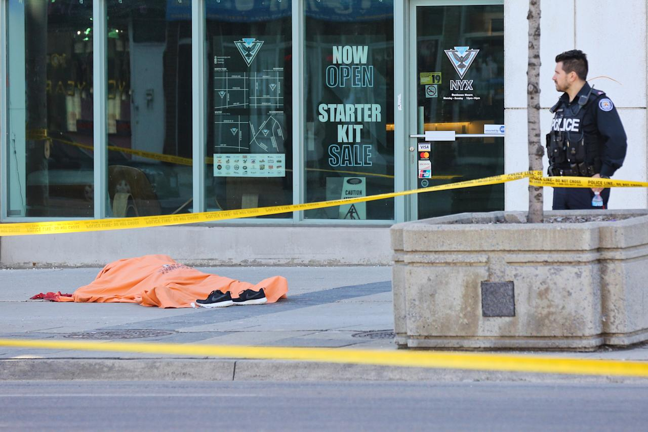 <p>A body lies on the pavement covered in an orange tarp after a deadly van strike in Toronto. Photo by Creative Touch Imaging Ltd./NurPhoto </p>