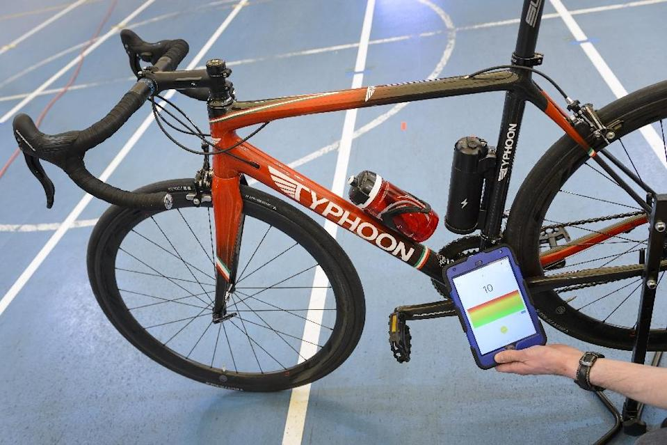 A staff member of the International Cycling Union (UCI) holds a tablet to scan a bicycle during a demonstation on testing technological fraud and detecting the presence of a motor inside the frame at the UCI headquarters in Aigle on May 3, 2016 (AFP Photo/Fabrice Coffrini)