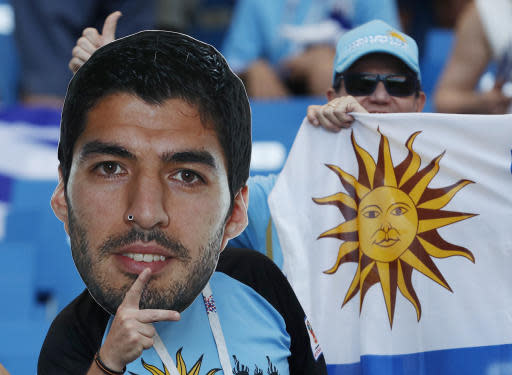 Uruguay's fan holds a portrait of Uruguay's Luis Suarez as he waits for the group A match between Uruguay and Saudi Arabia at the 2018 soccer World Cup in Rostov Arena in Rostov-on-Don, Russia, Wednesday, June 20, 2018. (AP Photo/Darko Vojinovic)