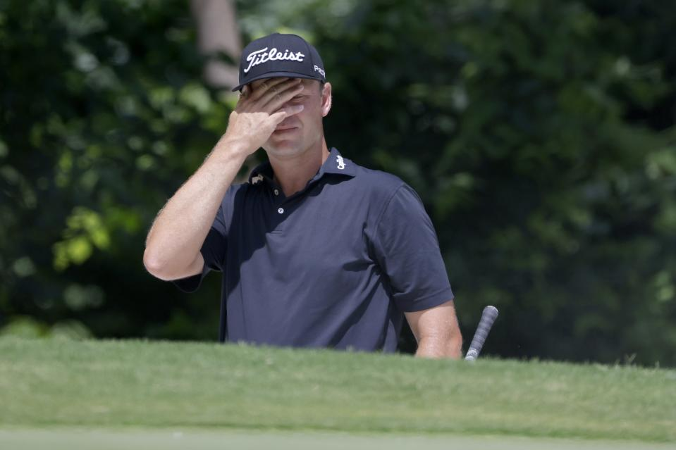Patton Kizzire wipes sand off his face after hitting out of a bunker onto the fifth green during the third round of the Charles Schwab Challenge golf tournament at Colonial Country Club in Fort Worth, Texas, Saturday, May 29, 2021. (AP Photo/Ron Jenkins)