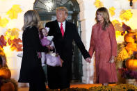 President Donald Trump and first lady Melania Trump pose for a photo with White House press secretary Kayleigh McEnany, holding her 11-month-old daughter, as they greet trick-or-treaters on the South Lawn during a Halloween celebration at the White House, Sunday, Oct. 25, 2020, in Washington. (AP Photo/Manuel Balce Ceneta)