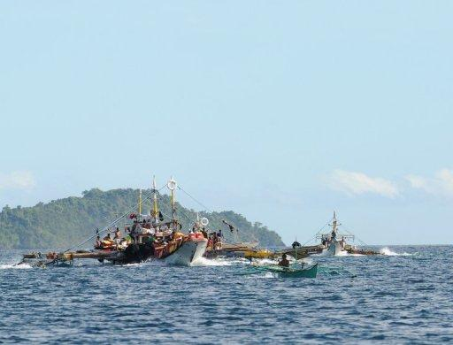 Philippine fishermen aboard their motorised boats sail along Ulugan Bay, in Puerto Princesa, Palawan island