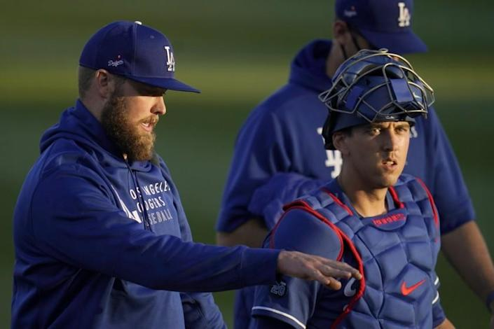 Los Angeles Dodgers pitcher Jimmy Nelson, left, talks with Dodgers catcher Austin Barnes after the two warm up in the bullpen prior to a spring training baseball game against the Chicago Cubs Thursday, March 4, 2021, in Phoenix. (AP Photo/Ross D. Franklin)