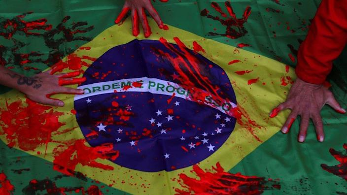 Black movement activists put their hands, covered by red paint, on a Brazilian flag, during a protest against racism and police violence in Sao Paulo